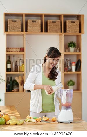 Smiling Asian woman pouring milk in shaker to make cocktail