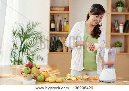 Cheerful lady making healthy cocktail for breakfast