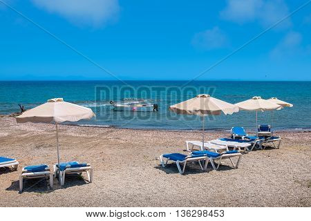Deck chairs and parasols on a beach. Aegean Sea Rhodes Dodecanese Islands Greece