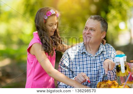 Father with daughter enjoying on picnic sitting on a bench