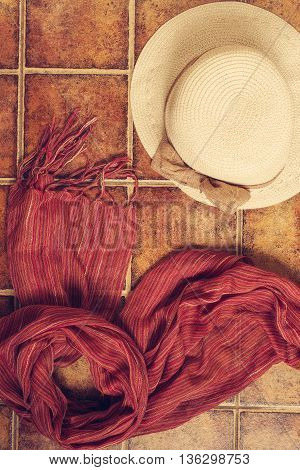 Straw hat panama hat with a red scarf lying on the tiled brown background. Vertical image.
