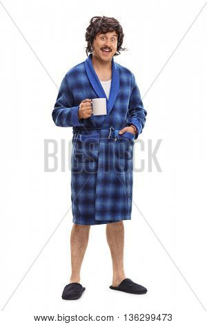Full length portrait of a relaxed man in blue bathrobe holding a cup of coffee isolated on white background