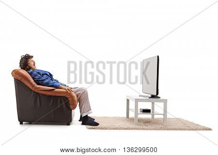 Scared man watching a horror movie on TV seated in an armchair isolated on white background