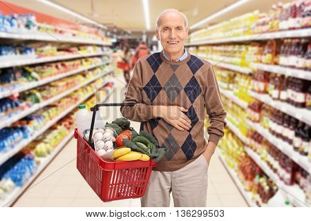 Senior shopping and posing in a supermarket with a basket full of groceries