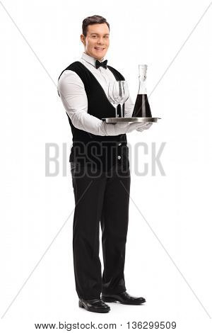 Full length portrait of a young male waiter carrying a tray with red wine and two glasses isolated on white background