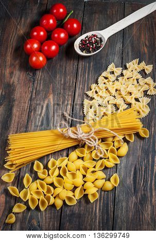 Italian pasta on a wooden table. Bunch tomatoes and spoon with spice. Top view.