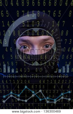 Hacker with black balaclava over a screen with binary code