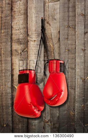 Pair of red boxing gloves hanging on wooden wall
