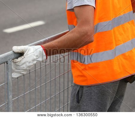 Worker With High Visibility Reflective Jacket Moves Iron Hurdles On The Road