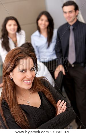 Business woman and her team behind her at an office