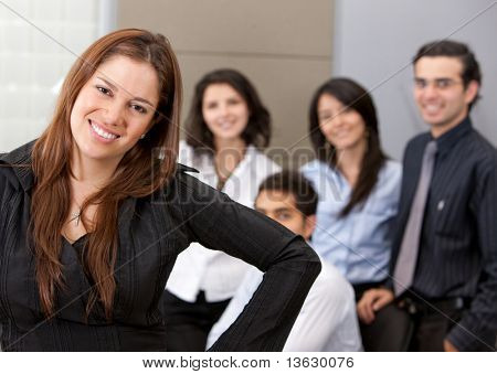 Business woman smiling with her team in an office