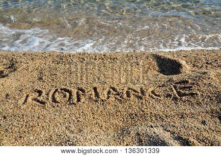 Word ROMANCE written on golden beach sand