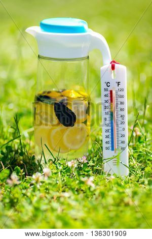 Warm summer day thermometer next cold lemonade showing high temperature