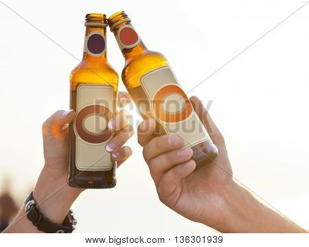 Couple on the beach having party drinking and having fun in the sunset holding bottles in their hands with the sun shining through