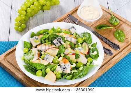 grilled chicken breast grapes celery spinach cheese and apple salad on a white dish on a cutting board with fork and knife view from above close-up