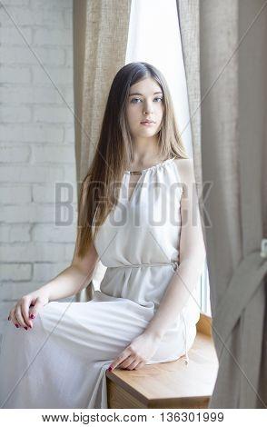 Portrait of a pretty teenage girl sitting on windowsill