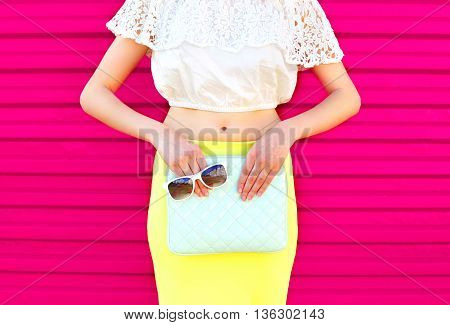 Fashion Glamour Woman With Handbag Clutch And Sunglasses Over Colorful Pink Background