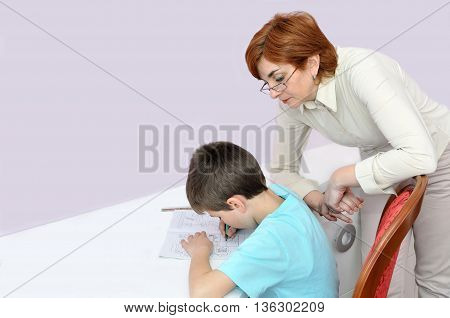 Woman helping young schoolboy to do his homework. Background with copy space on the left side.