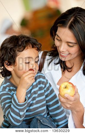 Woman and son at a supermarket eating fruits