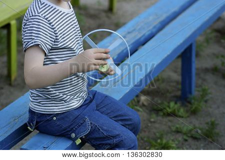 The image of the boy sitting on the blue old bench. In the hands of a boy toy spinner.