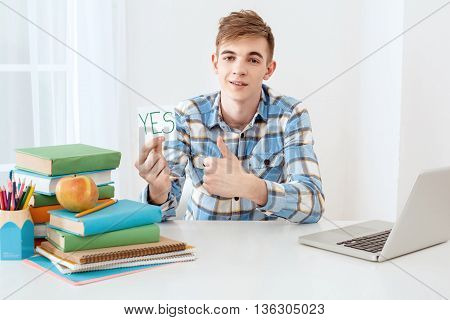 Modern problem: youth and computers. Young student using laptop and looking at camera. Guy holding sticker with word yes. Nice white interior with table full of books