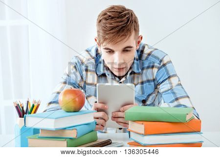 Modern problem: youth and computers. Young student using tablet computer while studying. Nice white interior with table full of books