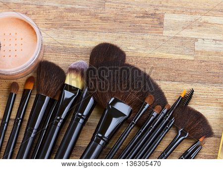 Set of black make up brushes on wooden table, top view