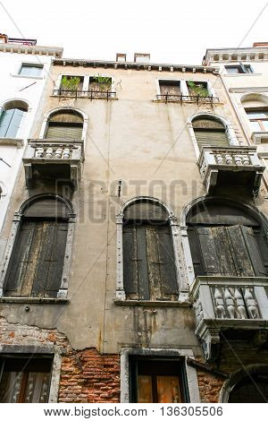 The narrow house on the street of Venice. Arched windows with black shutters collapses plaster and plants on the top floor.