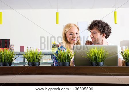 A beautiful young couple sitting in a coffee shop and using a laptop