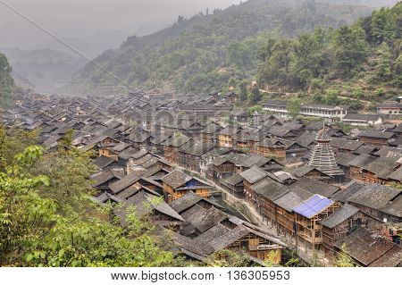 Zhaoxing Dong Village Guizhou Province China - April 7 2010: Tile roofs of wooden houses in the mountain village of Dong ethnic minority misty morning spring.