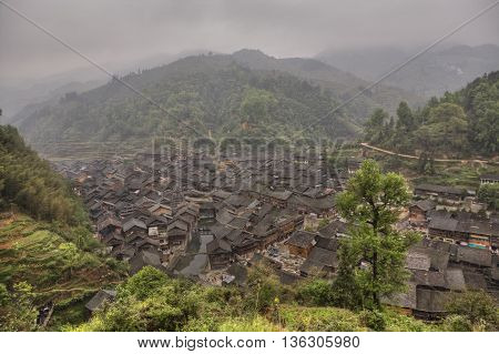 Zhaoxing Dong Village Guizhou Province China - April 7 2010: Panoramic picture of the ethnic minority settlements with wooden houses and tiled roofs in the mountainous area of southwestern China.