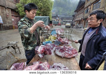 Zhaoxing Dong Village Guizhou Province China - April 8 2010: A street vendor weighs pork on Chinese scales.