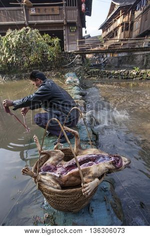 Zhaoxing Dong Village Guizhou Province China - April 8 2010: Asian man gutted the dog on the bank of a rural river and put it in a large wicker basket.