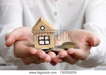 man holds in hands money with a home