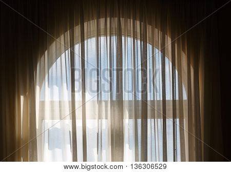 Transparent curtains on the window with arch. Sunlight streaming through the window with a transparent curtain.