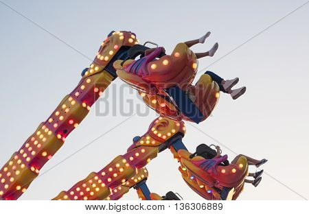 Hanging funfair attraction with people having fun. low angle view