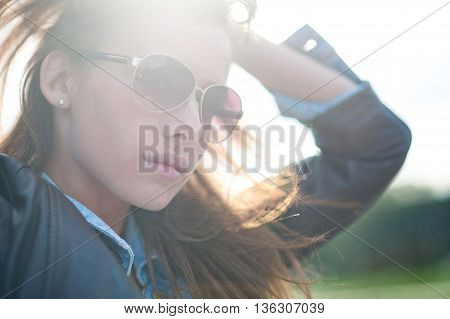 Outdoor portrait of beautiful girl with sunglasses