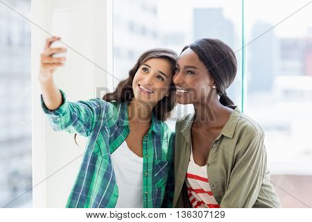 Happy friends taking selfie on a mobile phone