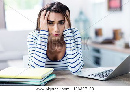 Portrait of tensed woman with head in hands sitting with laptop at table