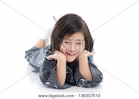 Happy asian boy in kimono lying on white background isolated