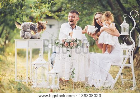 father, mother and daughter together at the picnic in the garden