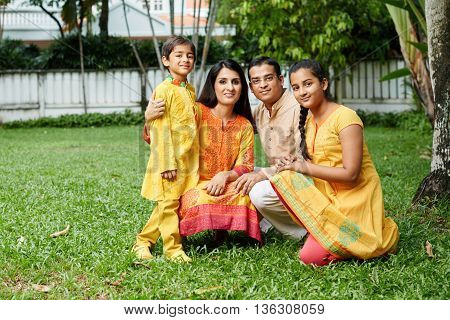 Happy family in national Indian costumes in backyard