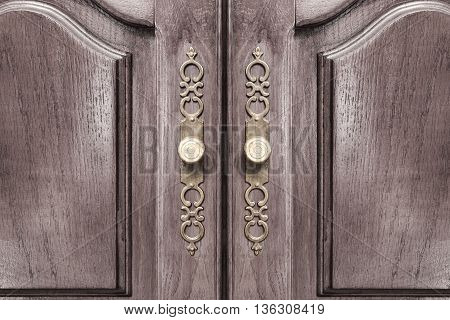 Stylish brass door handles on a hardwood cabinet or closet with ornate escutcheons and raised panels on the doors in a close up frontal view conceptual of furnishing and interior decor