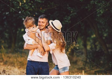 Happy family. Father, mother and daughter in the park