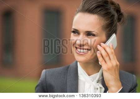 Smiling Business Woman Near Office Building Talking Smartphone