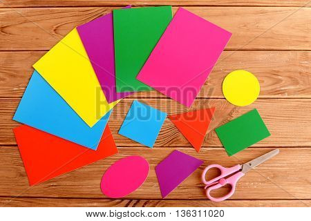 Paper basic geometric shapes for children education. Triangle, square, oval, trapezoid, rectangle, round. Sheets of colored cardboard, scissors on a wooden table