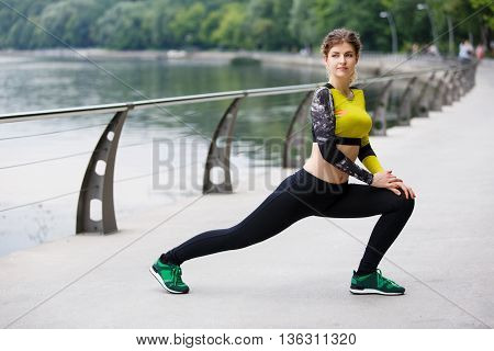 Young beautiful woman doing exercise on citys promenade