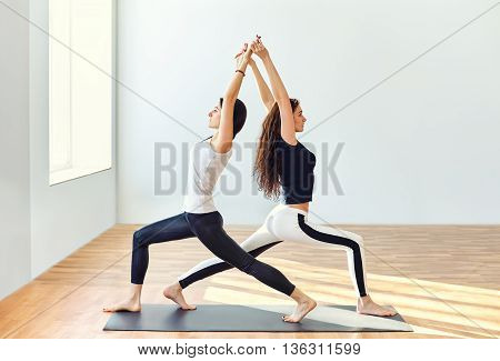 Two Young Women Doing Yoga Asana Warrior One Pose