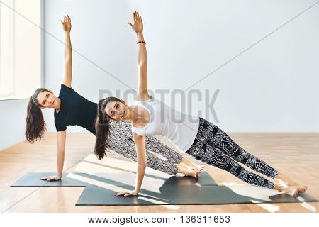Two Young Women Doing Yoga Asana Side Plank