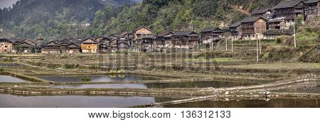 Zhaoxing Dong Village Guizhou Province China - April 8 2010: Panoramic view of village ethnic minorities in southwestern China wooden huts on background of mountains near rice fields spring.